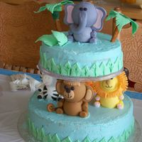 Amazon Shower Cake Yellow cake dyed blue, covered with buttercream, all animals made from fondant. gumpaste/fondant palm trees with pretzel rod