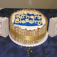 "Father's Blessing Cake Double layer 10"" rounds, Kalua fudge and white Kalua, covered in cream cheese frosting and surrounded with pirouettes and gold ribbon..."