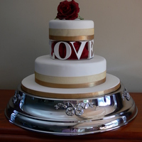 'love' Wedding Cake Choc Mud cake with whipped chocolate ganache filling. Covered with fondant. The stand is made from wooden laser cut letters, painted and...