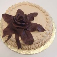 "Chocolate Rose & Leaves Cake 8"" round cake covered in Swiss Buttercream frosting. Piped edge trims. Rose, leaves and bow are in chocolate modeling paste (melted..."