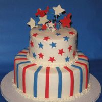 "Stars And Stripes Two-tiered 6"" and 10"" iced in buttercream, decorated with fondant stars and stripes, topped with gumpaste stars. It was done for..."