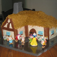 Snow White And The Seven Dwarfs Cottage cake iced w/ bc w/ mmf accents. RKT chimney covered in mmf. The figures were purchased.