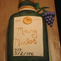 Wine Bottle Chocolate 9x13 carved into a wine bottle, covered in mmf and all accents are mmf. Wine bottle dusted w/ luster dust