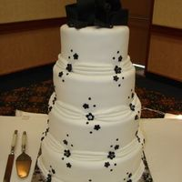 Black & Diamonds A 4 tier wedding cake covered in mmf. Decorations made with mmf with edible sugar diamonds. The bride gave me a picture of this cake but I...