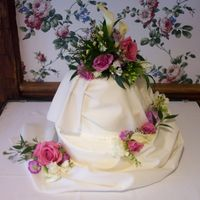 Draped Wedding Cake A draped cake trimmed with fresh flowers. I do not care for fondant, so the drape was real material matched to the soft ivory colored...