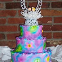 Tye-Dyed Wedding Cake tye-dyed wedding cake done with airbrush and sugar smiley faces set into the daisy shapes.