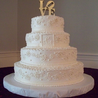 Ivory & Gold Outlined Blossom Wedding Cake  All ivory buttercream with outlined blossoms highlited with gold dust. Each tier was wrapped with ivory ribbon. The monogram was piped...