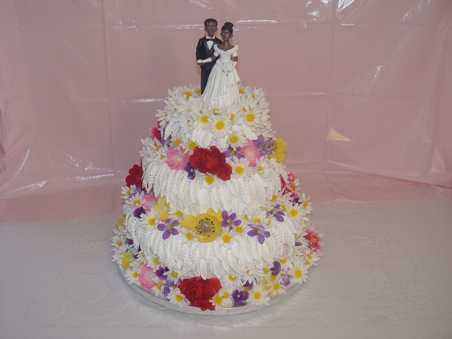 Multi Flower Wedding Cake   Leaves are made with royal icing. the bride want something different. what do you think.