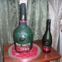 "Remy Martin Bottle  4-6"" cakes and 1/2 of the sports ball pan. For the neck of the bottle I used rice krispies.Covered in fondant and painted with gold..."