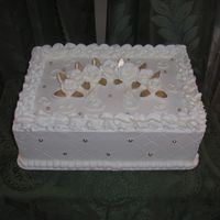 White Roses   1/4 sheet, french vanilla, buttercream, and gold dragees, and fondant leaves