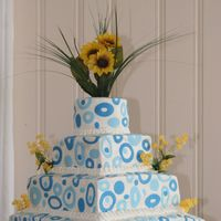 Wedding Cake With Fondant Circles This cake was designed by the bride and me. She wanted to capture the sunflower theme and the bridemaid's blue colors.