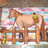 Horse Cake With Fence  Horse is Dark Chocolate Fudge cake with buttercream icing covered with MMF. Fence is stryfoam covered with MMF and painted. I added flowers...