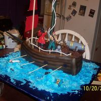 Pirate Ship  13 x 9 pan carved into ship. covered with chocolate mmf. airbrushed. water is buttercream icing. pirates and accesories are toys from...