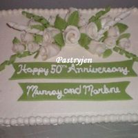 50Th Wedding 9x13 white cake iced with a whipped cream icing, fondant duff roses, leaves and ribbons.