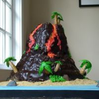 Volcano  I'm sticky, I'm tired, but it's done. It's a chocolate volcano cake for 20 people on a blue fondant covered board....