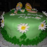 Angela_Cake_002.jpg Fondant covered cake with buttercream grass and royal icing daisys. Fondant/gumtex fairies.