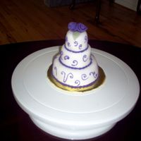 Three Tier Mini This miniture wedding cake was covered in fondant and accented with royal icing