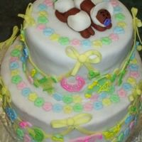"Tiiered Cake For Twins  This is a tiered cake with baby clothes on the ""line"" and twins on top. Flower ""buttons"" adorn the top and bottom of..."