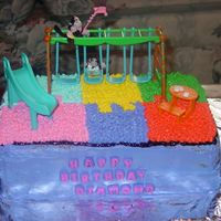 Playground Cake  This cake features the playground interlocking mat with a swing, a slide and a picnic table. All done in buttercream (excluding the toys...