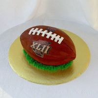 Super Bowl Xlii Football Yellow cake with chocolate icing. Made from a 9x13 sheet that was cut in half, stacked and carved. All buttercream with fondant accents....