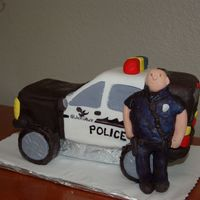 Police 10 inch square pan cut in half for the car. wheels are ding dongs covered in fondant. Police officer is made of fondant