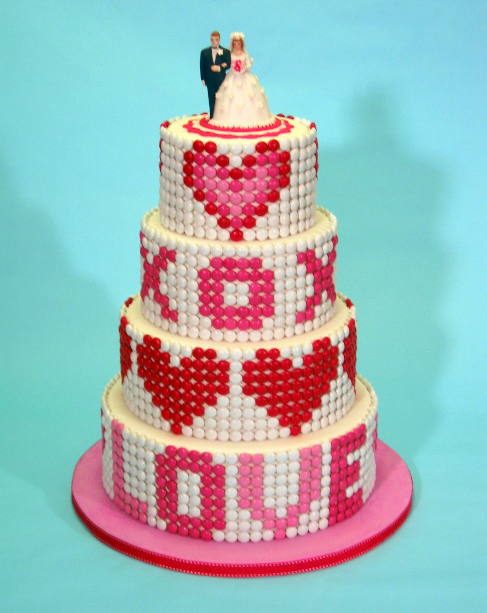 My Candy Valentine Red, pink and white M&M candies adorn the outside of this romantic Valentine's Day wedding cake.