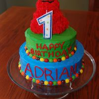 Elmo First Birthday Cake All buttercream, Elmo made with the Wilton Small Bear Pan (carved a little) with grass tip for fur. Skittles border