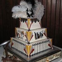 Art Deco Wedding Cake Cake covered in white chocolate and fondant mixture. There are hand drawn panels on all four sides of the second layer. Ostrich feather...