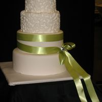 "Wedding Cake For A Bridal Show This cake is 6-8-10-12 rounds. The ""lace"" is made using a mold with fondant. The ribbon is satin and there is a little sparkly..."
