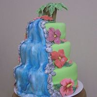Luau_Cake.jpg This was for my best friend's daughter's graduation party. The flowers and trees were gumpaste, the rest was fondant. I also made...