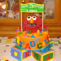 "Elmo Four baby blocks with 10"" on top. Elmo is rice crispy with bc fur. Accents are fondant."