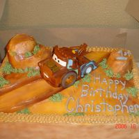 Tow Mater Tow mater on the dust road. buttercream that is airbrushed and cupcake hills. Tow Mater is a purchased toy.
