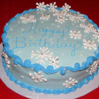 Winter Birthday Birthday cake for a lady whose birthday is the week before Christmas. Cake is iced in buttercream. Snowflakes are royal icing with dragees...