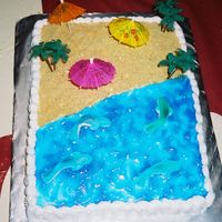 Luau Anniversary Cake buttercream icing,water is tinted piping gel, sand is graham crackers,and i had gummi sharks in the water