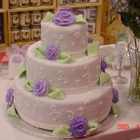Purple Rose Wedding Cake Cake is covered with lavender fondant. Purple royal icing roses and green fondant leaves adorn the 3 tiers.