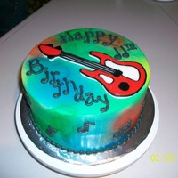 Tie Dye Guitar Chocolate cake with all butter buttercream, air brushed tie dye and royal icing guitar.
