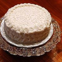 White Cake This is a white cake with strawberry filling and buttercream frosting. The top is cornelli lace and the border and sides are supposed to be...