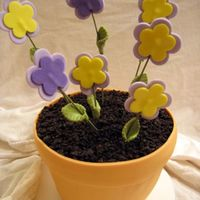 Flower Pot  I did two of these for friends. The flowers and flower pot are made of mmf, the cake is chocolate with chocolate buttercream, and the dirt...