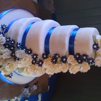 Cascading Flowers Fondant covered wedding cake with cream colored handmade roses and sapphire blue blossoms cascading down. The bride's sapphire...