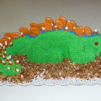 "Dinosaur Cake Chocolate cake with buttercream icing, candy corn ""baby"" spikes, chocolate chip claws, red hot eyes and toasted coconut for &quot..."