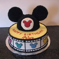 "Mickey Mouse Cake 10"" white/chocolate filled and iced with bc. Mickey hat is chocolate cake iced with choc bc. The colored mickey's on the sides..."