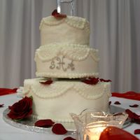 White Wedding Cake With Cornelli Lace This is a 3-tiered white cake with white buttercream, Cornelli lace on the op and down the sides with pearl borders all around and a silver...