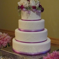 Purple & White Fondant with purple ribbon, real white roses and mini lights. So beautiful at night.