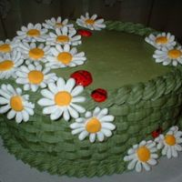 Cakewladybugs3.jpg   A buttercream basketweave cake with daisies and ladybugs made from royal icing.