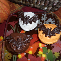 Chocolate Bat Cupcakes  Vanilla and chocolate cupcakes frosted with milk chocolate and vanilla (food colored orange). Homemade bats are semi-sweet chocolate...