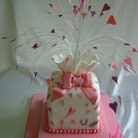 Large Parcel Cake A large stacked parcel cake covered in fondant, with a large sugar bow and heart/glitter topper......