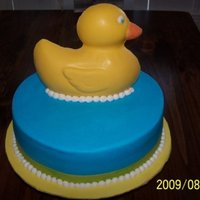 Ducky Baby Shower  12 in. round cake iced in butter cream. Yellow band at the bottom is ribbon. Duck is made out of chocolate using the wilton duck pan as a...