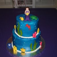 Mermaid/under The Sea Cake   8 in. and 6 in cakes. Iced in butter cream and airbrushed blue. Decorated with fondant accents. Stars are made from chocolate.