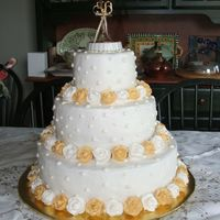 50Th. Anniversary Butter cake torted with raspberry filling. Roses are royal icing airbrushed gold.
