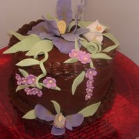 Chocolate Cake W/ Iris & Orchid   The cake is Chocolate w/ dark Chocolate Buttercream, flowers are all fondant